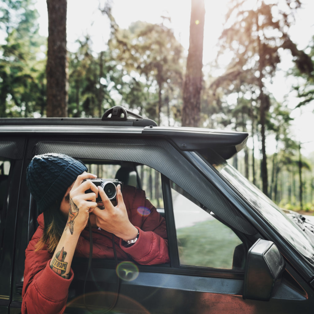 guy taking photos outside of his car while on a road trip