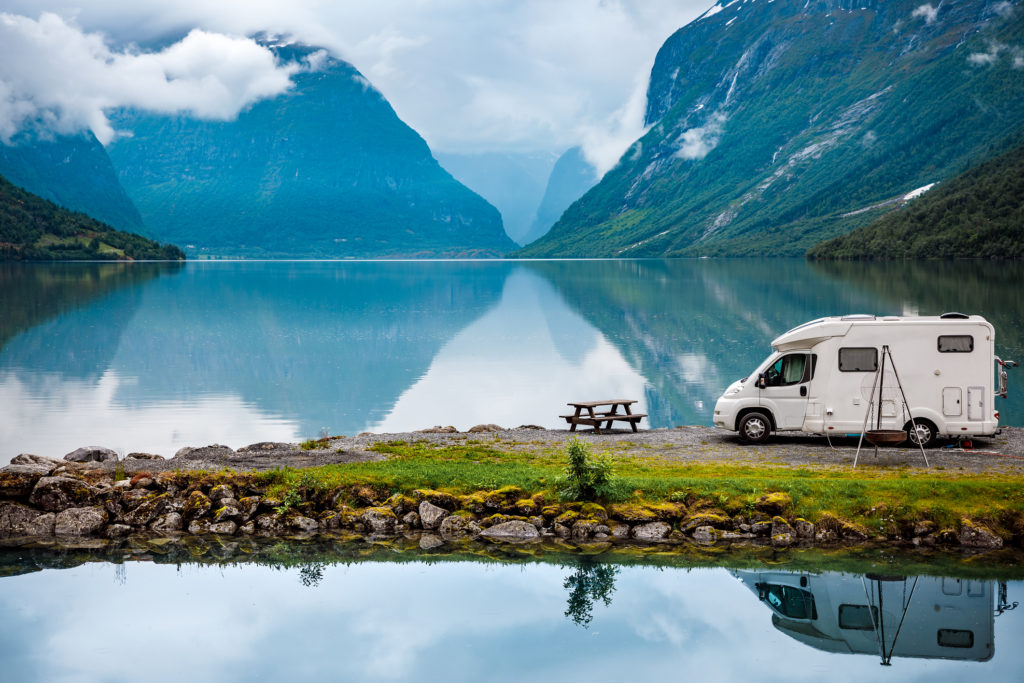 RV parked on lot with scenic lake and mountains in background