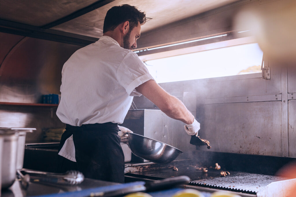 man working inside of a food truck