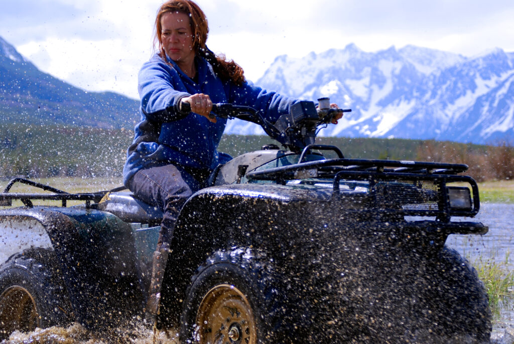 woman on an ATV with mountain in the background