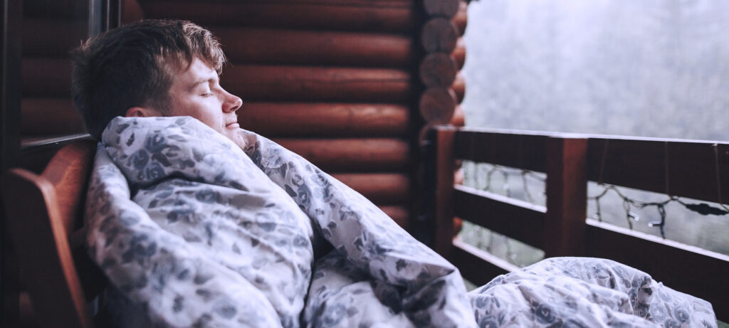 young man wrapped in blanket on outdoor porch